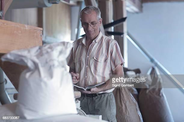 male miller monitoring sacked flour at wheat mill - sigrid gombert imagens e fotografias de stock
