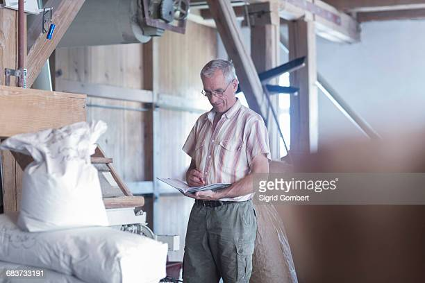 male miller monitoring sacked flour at wheat mill - sigrid gombert stock-fotos und bilder