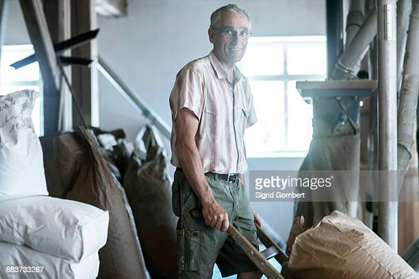male miller pushing sack barrow at wheat mill - sigrid gombert imagens e fotografias de stock