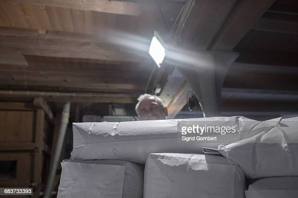 male miller stacking sacks of milled flour in wheat mill - sigrid gombert stock-fotos und bilder
