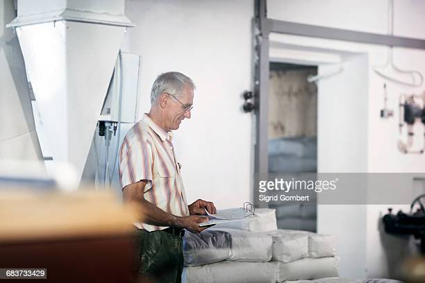 male miller stock taking sacks of flour at wheat mill - sigrid gombert imagens e fotografias de stock