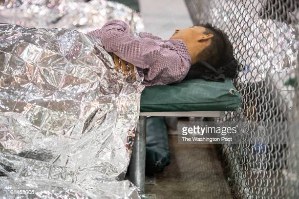 Male minor rests under mylar blankets in the US Border Patrol Central Processing Center in McAllen, Texas on August 12, 2019. Border Patrol officials...