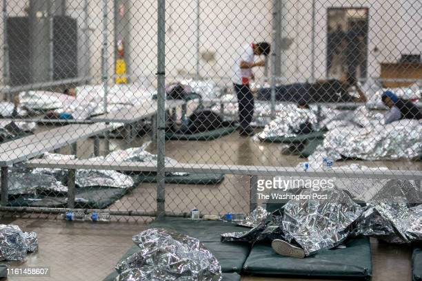 Male minors rest under mylar blankets in the US Border Patrol Central Processing Center in McAllen, Texas on August 12, 2019. Border Patrol officials...