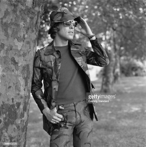 Male model in a camouflage jacket and matching trousers and hat, UK, August 1971.