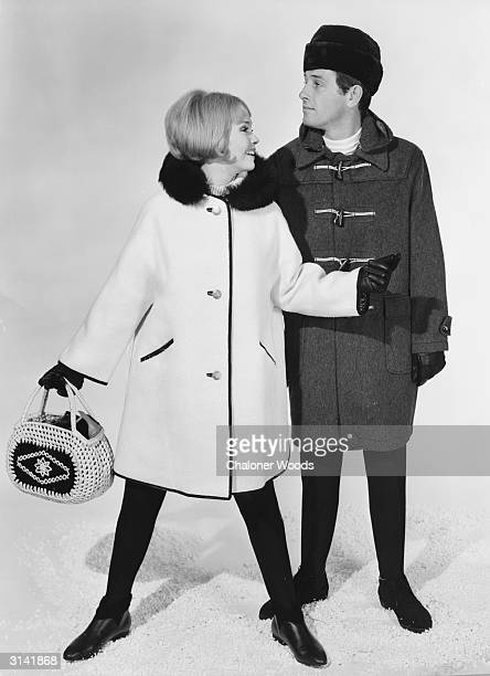 A male model is dressed in a toggle fastened duffel coat worn with a Russian type fur hat His partner is in a woollen threequarter length coat with...
