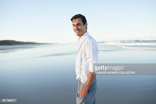 male model on beach smiling at camera in suit - サスペンダー ストックフォトと画像