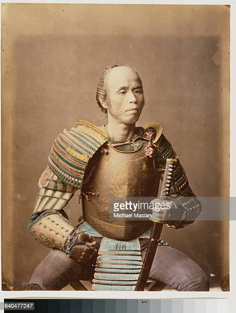A male model poses as a samurai wearing armor and holding a katana Japan ca 1890s