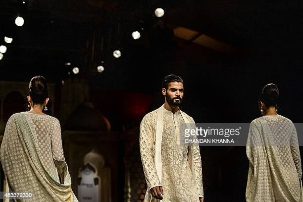 A male model presents a creation by Indian designers Abu Jani and Sandeep Khosla during the BMW India Bridal Fashion Week 2015 in New Delhi on August...