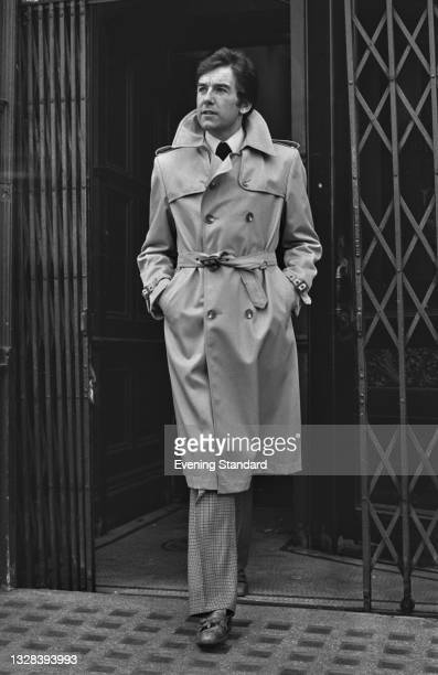 Male model wearing a belted trenchcoat, UK, 11th September 1974.