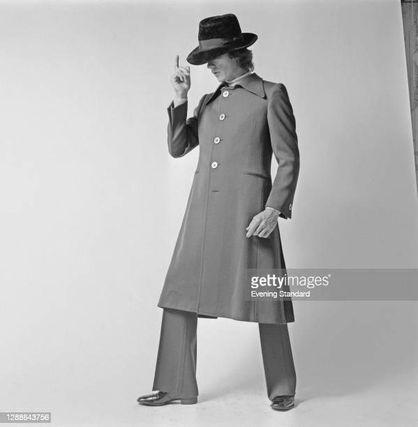 Male model wearing a calf-length coat and a hat, UK, 1971.