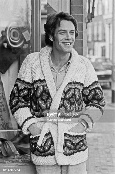 Male model wearing a chunky knitted cardigan with a matching belt, UK, 16th January 1974.