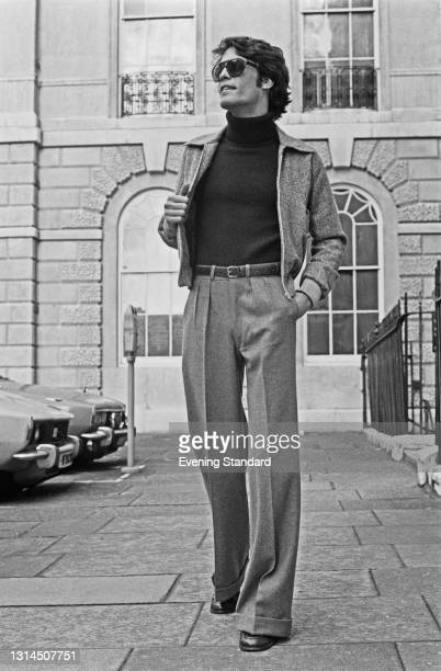 Male model wearing a waist-length jacket and creased trousers, UK, 16th January 1974.