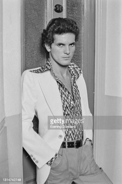 Male model wearing a white jacket over a geometric patterned shirt, UK, 12th June 1974.