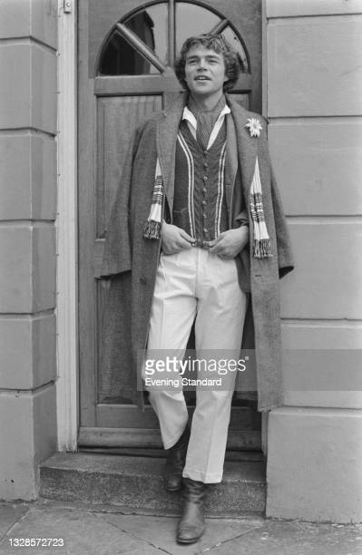 Male model wearing white trousers and a long tweed coat and scarf, UK, 6th November 1974.