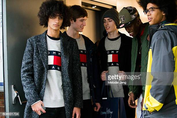 Male models after the Tommy Hilfiger show in Tommy Hilfiger logo sweatshirts at Cedar Lake during New York Fashion Week Men's Fall/Winter 2016 on...