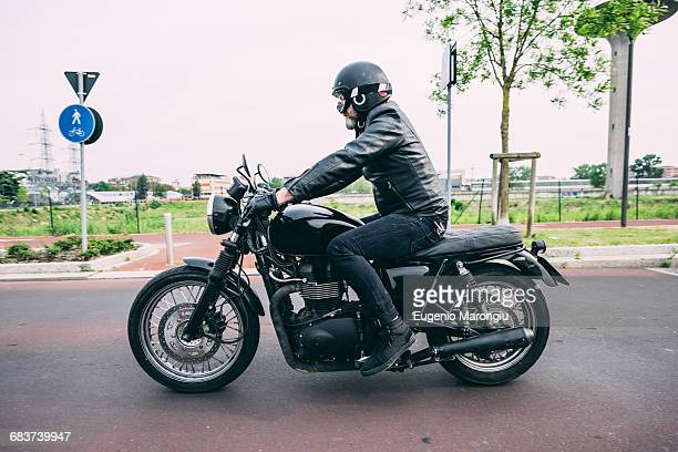 Male motorcyclist motorcycling on road
