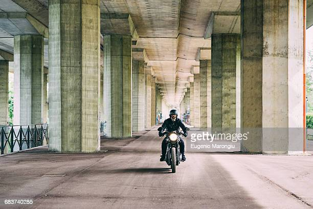 Male motorcyclist motorcycling under flyover