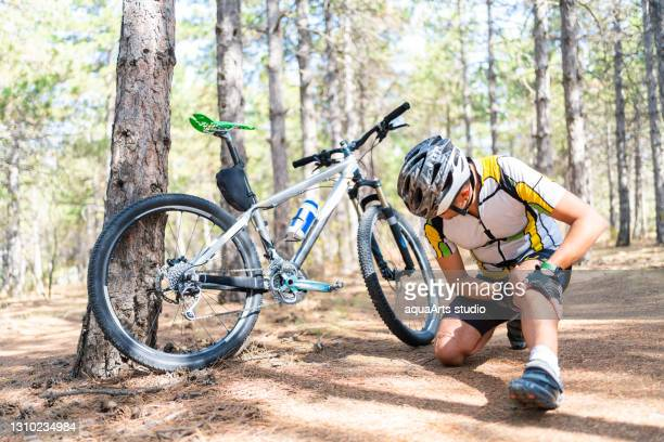 a male mountain bicycle rider injured while out on a bike ride in nature - injured stock pictures, royalty-free photos & images