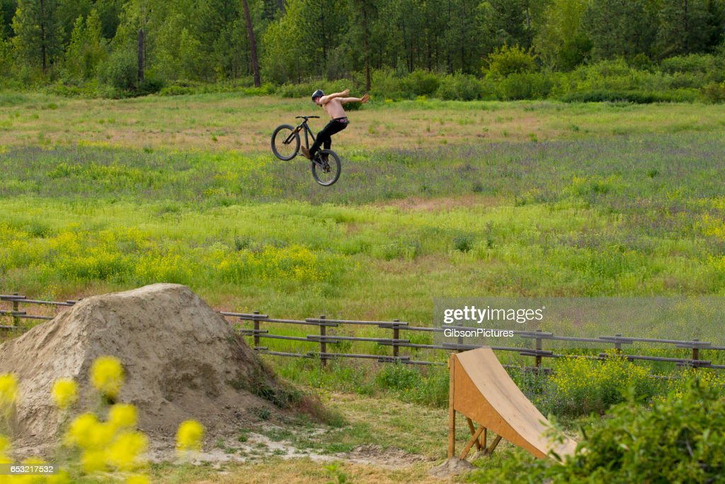 A male mountain bike rider does a no hander trick off a big jump in the summertime. : Stock Photo