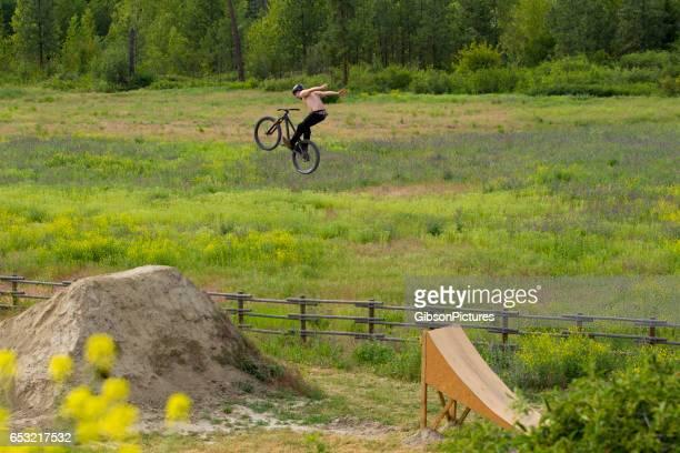 Un coureur de vélo de montagne mâle ne fait un aucun tour de virage hors un grand saut en été.
