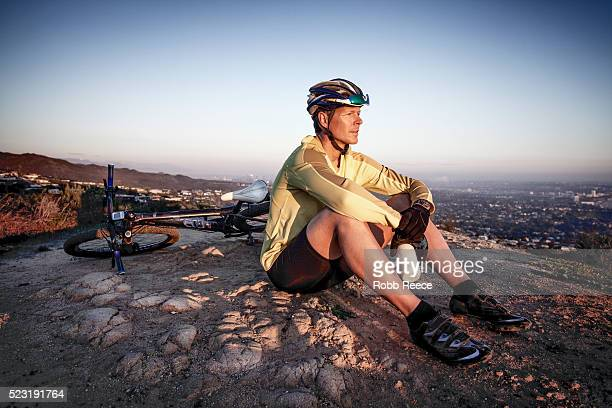 a male mountain bike rider sits and rests during a trail ride while overlooking a city - robb reece bildbanksfoton och bilder