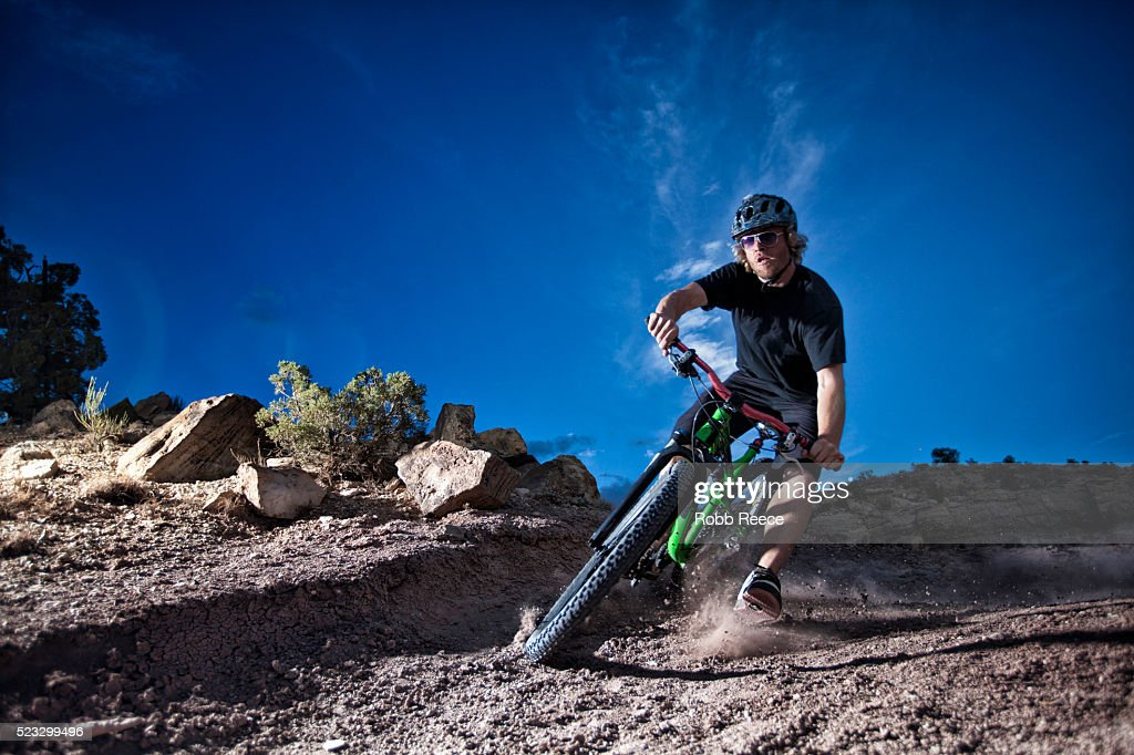 A male mountain bike rider speeds around a steep, dirt curve on a single track trail : Stock Photo