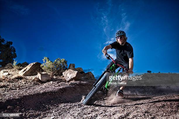 a male mountain bike rider speeds around a steep, dirt curve on a single track trail - robb reece 個照片及圖片檔