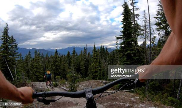 male mountain biker follows trail through forest - following stock pictures, royalty-free photos & images