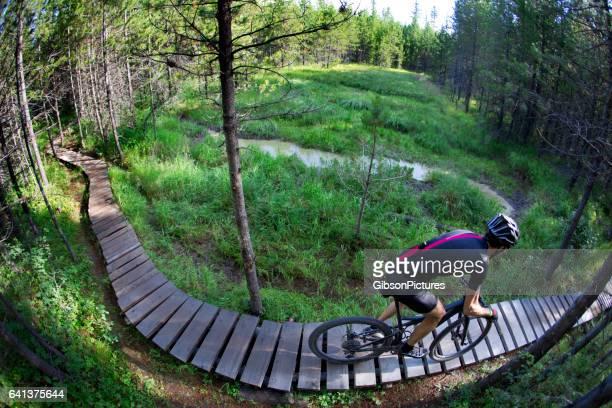 男性山のバイカーは、ブリティッシュ ・ コロンビア、カナダのクロスカントリー ・ レースで競争しながら狭い遊歩道を乗っています。