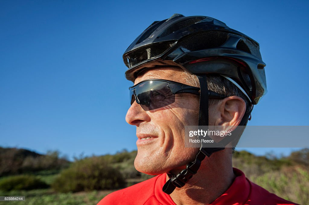A male mountain biker with helmet and sunglasses, standing and looking away : Stock Photo
