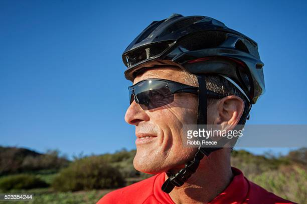 a male mountain biker with helmet and sunglasses, standing and looking away - robb reece stockfoto's en -beelden