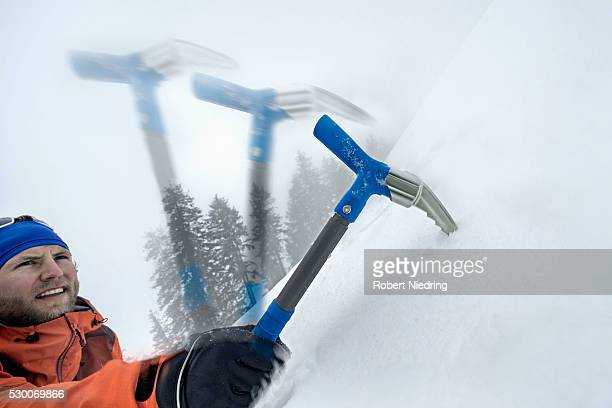 Male mountain climber going up snowy slope with axe, Zell Am See, Austria