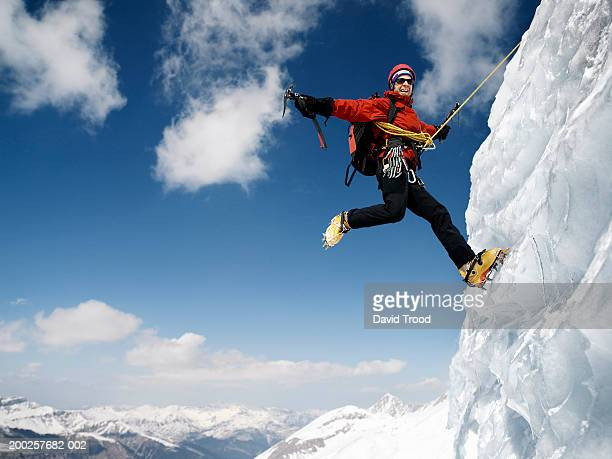Male mountain climber on ice-covered rock face, arms outstretched