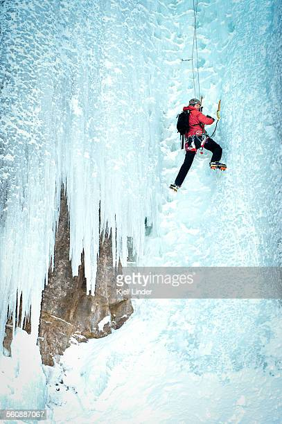 Male mountain climber scales icy waterfall