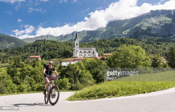 male mountainbiker in front of the church of dreznica, slovenia. - slovenia stock pictures, royalty-free photos & images