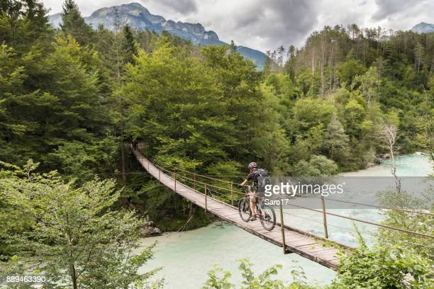 Male mountainbiker is crossing a suspension bridge in Slovenia.