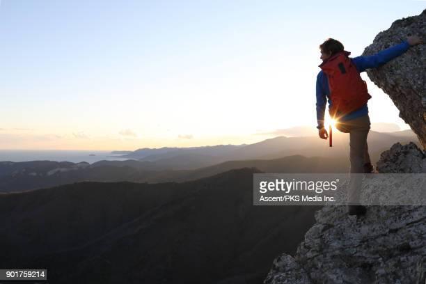 Male mountaineer pauses on rock ridge, near summit