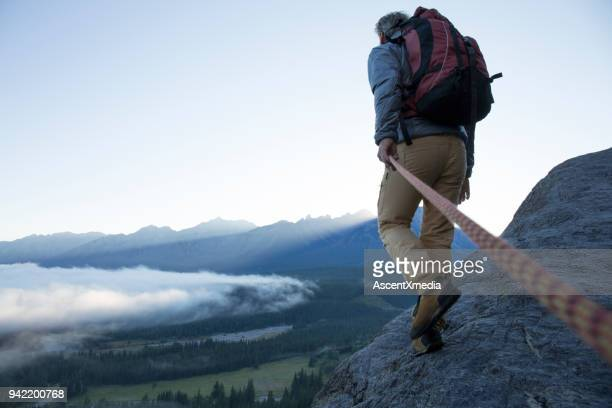 male mountaineer traverses mountain ridge at sunrise canadian rockies - dedizione foto e immagini stock