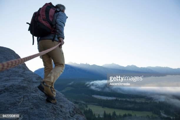 male mountaineer traverses mountain ridge at sunrise canadian rockies - beige pants stock photos and pictures