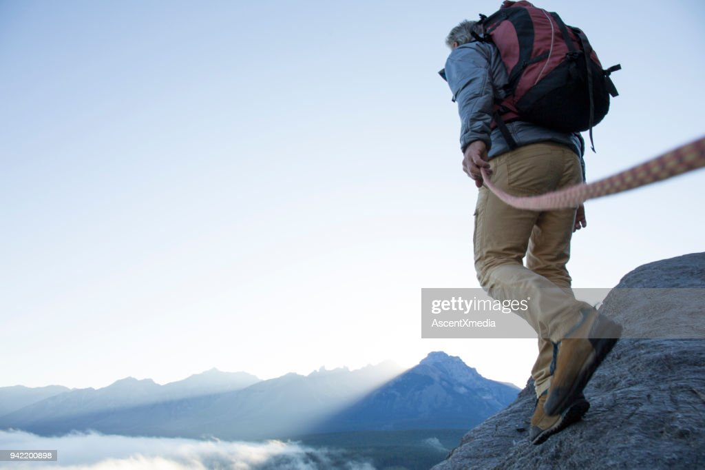 Male mountaineer traverses mountain ridge at sunrise canadian rockies : Stock Photo