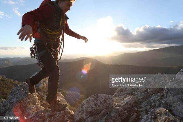 Male mountaineer traverses rock ridge, nears summit