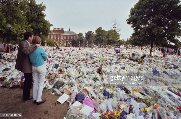 A male mourner puts his arm around a female mourner beside him as they stand before the floral tributes and messages of condolence in memory of...