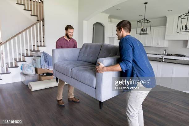 male movers carry sofa into home - two seater sofa stock pictures, royalty-free photos & images