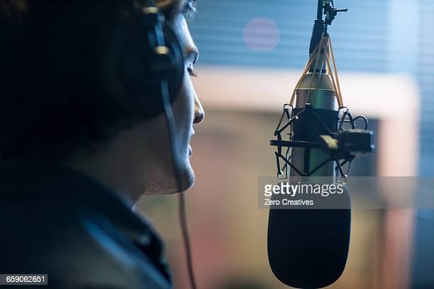 male musician in recording studio, singing into microphone - sound recording equipment stock pictures, royalty-free photos & images