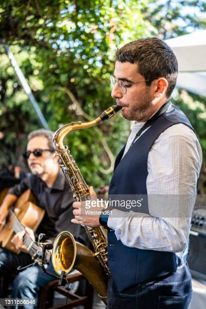 male musician playing saxophone - performance group stock pictures, royalty-free photos & images