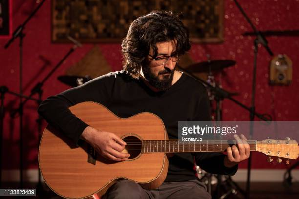 Male musician playng acoustic guitar in sound studio