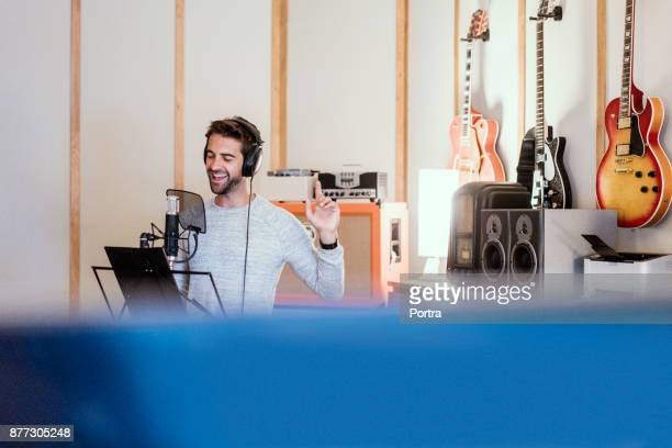 male musician singing into microphone in studio - producer stock pictures, royalty-free photos & images