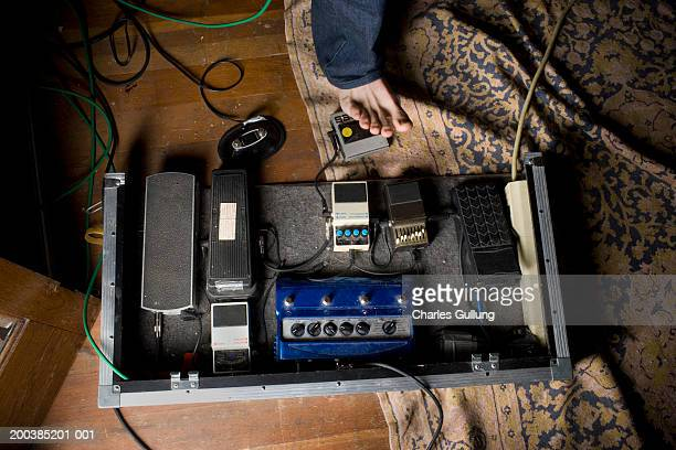Male musician using assorted effects pedals, low section
