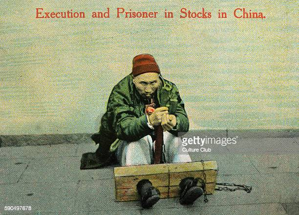 Male Muslim prisoner with feet shackled to wooden stocks China early 20th century