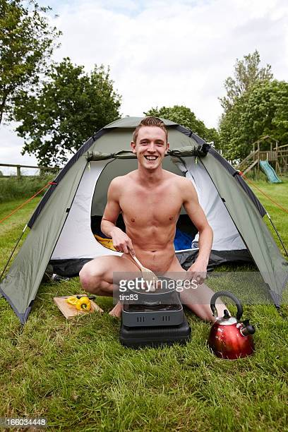 Male nudist cooking sausages on camping stove